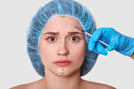 Scared attractive woman looking with fear directly at camera, getting injection in forehead, having black traits at chin made by marker pen, wearing blue medical cap, looks worried and confused.