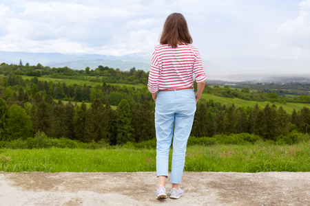 Woman standing in mountain, panoramic view of mountain range, trees. green grass. blue sky, female wearing casual trousers and white t shirt with red stripes enjoying beautiful nature. People concept.