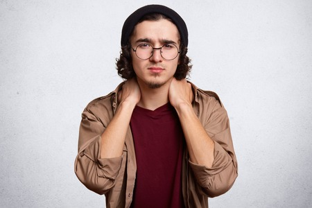 Indoor studio shot of handsome serious young guy posing isolated over white background in studio, touching his neck with both hands, doing massage, feeling pain aback, wearing casual clothes. Stock fotó