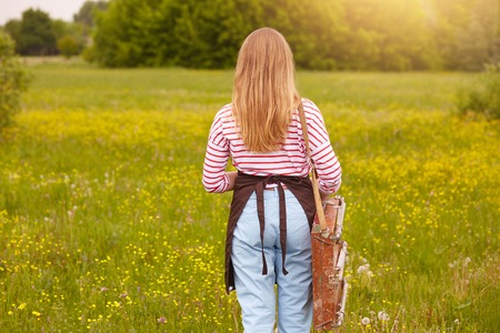 Back view of female artist finishing her picture on sketchbook, standing in front of beautiful nature, wearing striped shirt, pants and brown apron, female has long blonde hair. Art and creating concept.