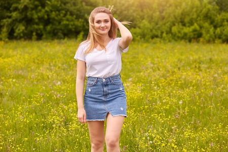 Outdoor shot of pretty blond woman wearing white casual t shirt and denim skirt, posing in meadow, touching her fair hair, looking at camera with pleasant facial expression. Happiness concept.