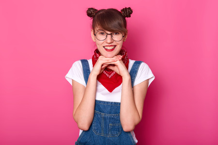 Adorable charming young student touching her chin with both hands, looking directly at camera, being cheerful, wearing round stylish eyeglasses, jeans overalls, red bandanna and white t shirt.