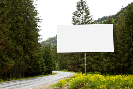 Empty billboard or big board on side of road with green forest and hills on background. Advertising blank, mock up, copy space for your advertisment or promotion text, Concept of advt and trading.