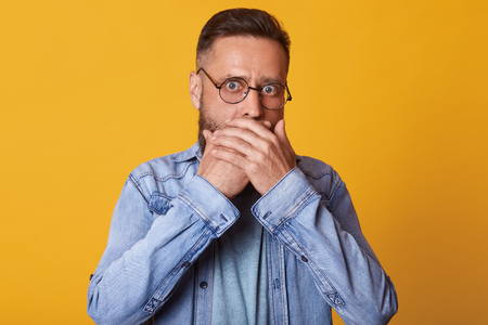 Shocked scared middle aged surprised face covering mouth with both hands, horrified stunned looking at camera isolated on yellow studio background, startled guy wearing denim jacket and gray jacket. Stock Photo