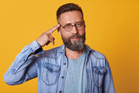 Studio shot of handsome middle aged male standing and doing suicide gesture, keeps fingers near temple, being in bad mood, has tired facial expression, posing isolated over yellow background.