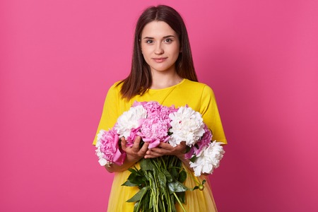 Portrait of tender magnetic black haired lady wearing bright yellow items of clothes, looking directly at camera, having good mood, holding bouquet of white and pink peonies. Spring concept.