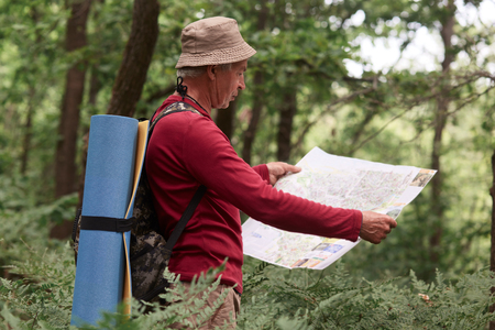 Image of old man traveling, having active rest, spending his vocation backpacking, standing with map, tries to find right way. Traveling, active recreation, adventure, spending time in open fresh air. Imagens