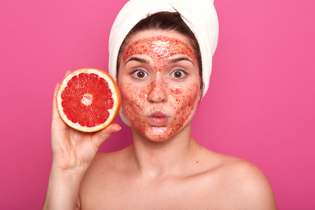 Surprised well kept young woman applied facial colorful scrub, looking directly at camera, holding half of grapefruit in one hand, putting her lips together, standing half naked in photo studio. Stock fotó
