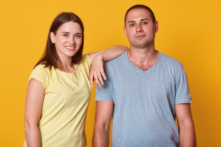 Studio shot of happy positive young couple looking and smiling at camera, girl wearing yellow t shirt standing with hand on mans shoulder, attractive male dressed gray casual shirt has pleased expression.