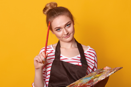 Indoor shot of thoughtful creative artist with paint equipment, touching head with brush, thinking over concept of masterpiece, standing isolated over yellow background in studio. Creativity concept.