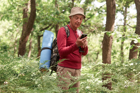 Experienced traveler holding his smartphone in one hand, using device for orientating, being alone, having compass and sleeping pad, wearing hat, trousers, sweatshirt, backpack. Travel concept.
