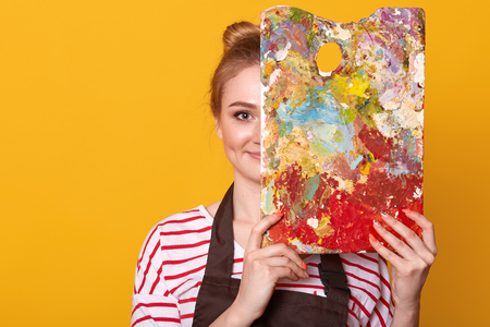 Indoor studio shot of satisfied talented girl holding palette to mix colors, covering half of her face with it, looking directly at camera, ready to paint masterpiece, being inspired by her hobby.