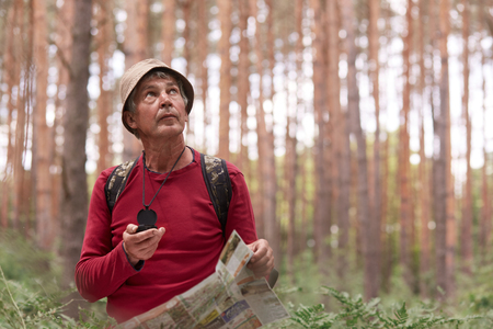 Close up shot of elderly man hiking and looking up at sky, using map and compass for direction for trip in forest, traveling around world, having adventure in wood, enjoying his active vacation.