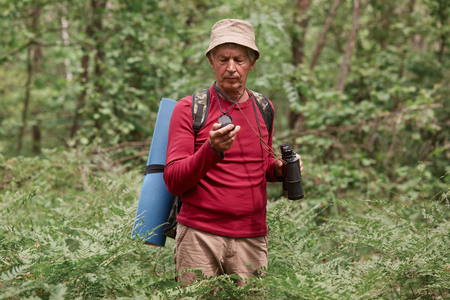 Portrait of senior man with binoculars and backpack standing in middle of forest, holding compass in his hand, looking attentively, practicing to orientate in unknown place, looking concentrated.