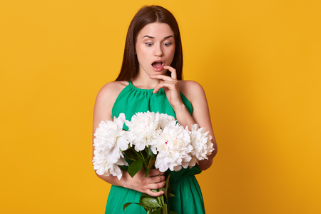 Surprised emotional lady looking at bunch of white peonies, opening her mouth and eyes widely, touching her cheek with finger, being impressed by spring present, guessing whose gift it must be.