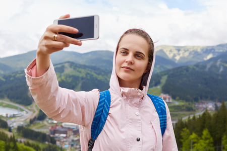Shot of pretty young female tourist makes selfie in mountain, woman traveler being photographed outdoor against beautiful landscape. Traveling, lifestyle, adventure and active vacations concept. Imagens - 124455218