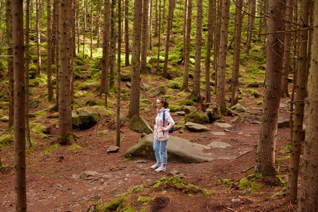 Outdoor shot of young girl walks alone in forest, woman in night jacket happily walks, being among trees, likes to spend time in open fresh air. Traveling, adventure, active vocation concept. Imagens - 124455238