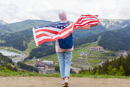 Outdoor shot of slim girl at nature background with American flag on her shoulders, woman wearing casual rosy jacket, trousers, sneakers and rucksack having vocation in mountains. Traveling concept. Imagens - 124455242