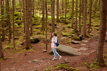 Profile of young European female wandering in forest around trees, green and stones, wearing light pink jacket, blue jeans, backpack and sneakers, looking aside, having sense of adventure. Travelling. Фото со стока