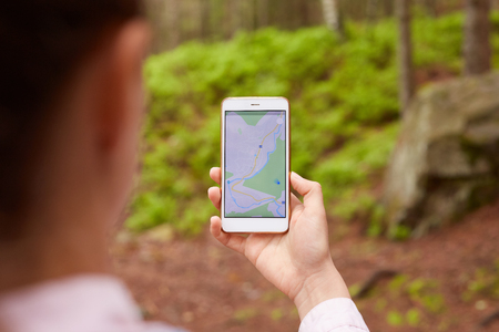 Woman standing in middle of nowhere, using navigation app on smartphone, following route with help of map, looking at device screen, using smartphone navigation while losing yourself in forest.