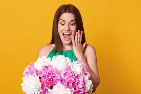 Beautiful cheerful girl stands isolated over yellow studio background, poses smiling and holding bouquet of peony flowers with astonished facial expression. Young happy woman. Surprise at birthday.