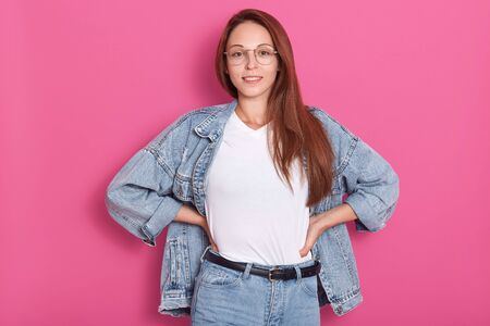 Close up portrait of young lady with denim clothing and spectacles, stands smiling isolated over pink studio background, keeps hands on hips, looking directly at camera. Fashion, people, jeans concept Фото со стока