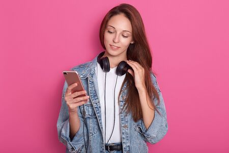 Young attractive girl standing isolated over pink background, holding her smartphone in hand, having headphones around neck and touches it with her fingers, looks at her device, wearing stylish outfit