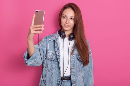 Attractive girl taking selfie against pink studio wall. Grinning woman in stylish denim jacket and basic whit t shirt, holding smartphone and listening music via earphones, looking at her device.