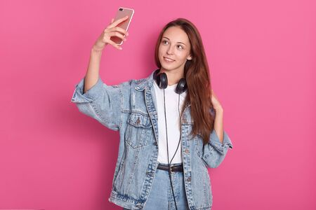 Portrait of pretty young woman in denim fashionable clothes, making selfie shot via mobile phone, having head phones around neck, has long hair, posing isolated on rose background in studio.