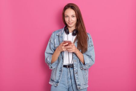 Portrait of happy beautiful young lady using her phone, looking directly at camera and smilng, wearing denim jacket, white shirt and jeans, having long straight hair, isolated over pink background. Фото со стока - 129221965