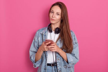 Charming woman with dar hair holding smartphone in both hands and looking at the camera over rose background, dressed stylish outfit, has head phones around neck, like to listen music, looks serious. Фото со стока - 129221966