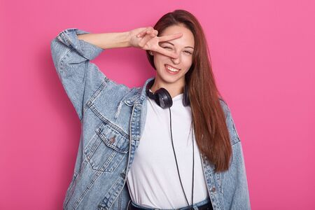 Front view of beautiful happy young woman looking directly at camera, holding peace sign near eye and standing isolated over rosy background, wearing denim jacket, holding headphones around neck. Reklamní fotografie