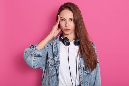 Indoor shot of young woman in denim casual clothes, holding headphones around neck, has headache from loud music, looks tired, keeping finger on temple, isolated on pink orange background in studio.