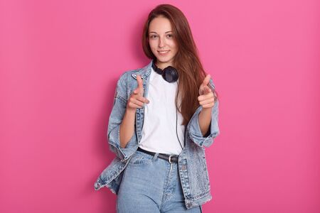 Positive cheerful young caucasian woman with long hair, wearing white casual t shirt, jeans and denim jacket, holding headphones around neck, pointing at camera with her index fingers and smiles.