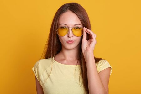 Horizontal shot of adorable woman wering casual outfit, keeps hand on her stylish sunglasses, having dark long straight hair, looking directly at camera with cunning facial expression. People concept. Reklamní fotografie