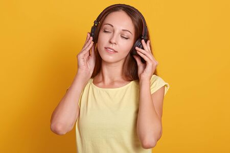 Close up portrait of beautiful Caucasian woman listening to music via headphone, relaxing while having free time, posing with closed eyes, dressed casual outfit, isolated over yellow studio background 스톡 콘텐츠