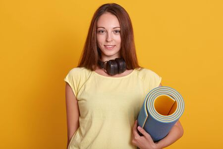 Close up portrait of young attractive woman with perfect body, wearing headphones arond neck and yellow t shirt, holding a water fitness mat, having long straight hair. Concept of fitness and sport. Reklamní fotografie