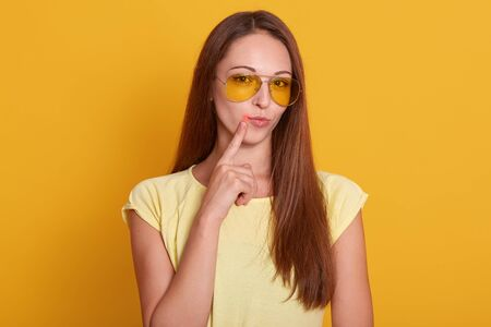 Close up portrait of beautiful dark haired woman points to her lips with fore finger, has virus, being infected with col sore herpes, needs treatment, dressed casually, isolated over yellow background