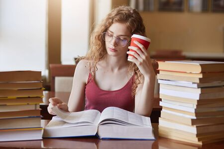 Tired determined college student searching for appropriate information for her project, reading texts, putting papercup of drink to her head, wearing red shirt and eyeglasses, working without stop. Reklamní fotografie
