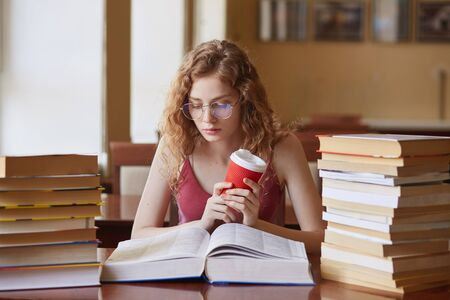 Education and school concept. Clever female student girl with coffee in hand, wearing glasses and casual outfit, looks concentrated, sitting at desk in college library with stack books reading.