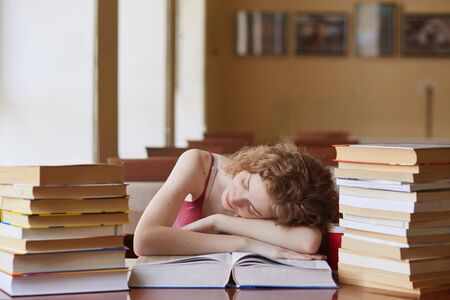 Foxy haired female student fall asleep while reading book for finding information, preparing for exams, woman laing at table, doing assignments in university library. Education, school concept.