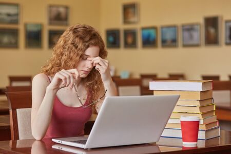 Close up portrait of axhuasted sad woman feeling tired sitting at table in reading room with laptop, being with her glasses off, keeps fingers on nose, looks unhappy. Education and university concept. Stockfoto