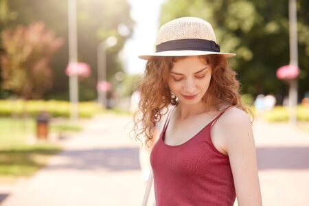 Sweet attractive young lady standing in middle of park, looking aside, enjoying time in fresh air, wearing casual summer clothes, being in romantic mood, almost closing her eyes. Rest concept.