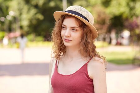 Closeup portrait of cute smiling lady having walk in park in summer day, being in high spirits, wearing hat with black stripe and red top, looking aside. People and free time activities concept.