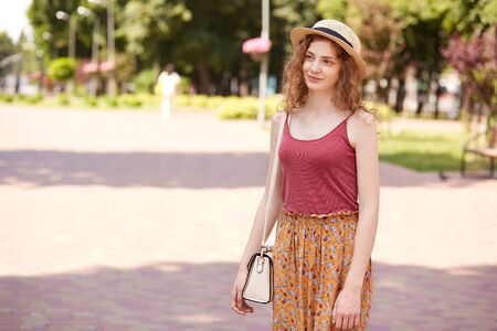 Outdoor shot of romantic adorable model with fair curly hair standing in local park, spending time around nature with pleasure, wearing hat, red top and colorful skirt, having white bag on shoulder. Reklamní fotografie