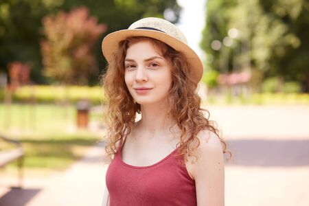 Closeup portrait of smiling beautiful girl posing in fresh air, having pleasant facial expression, standing around numerous trees and green, being in good mood. People and urban life concept.