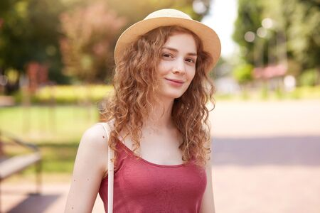 Outdoor shot of sweet attractive young female looking directly at camera, wearing straw hat and red top, having bag on shoulder, spending her weekends outside. People and activities concept. Reklamní fotografie