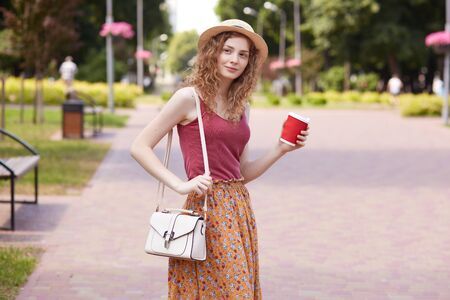 Image of attractive sincere sincere lady with curly hair standing in middle of green local park, having walk, stopping for coffee break, holding red paper cup with drink. Spare time concept. Reklamní fotografie