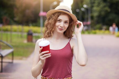 Close up portrait of a beautiful blond hair girl in vintage straw hat standing in park . Pretty tenderness model looking at camera.