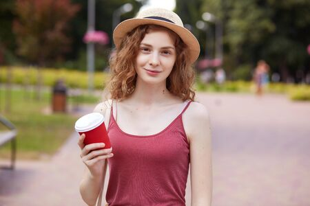 Closeup portrait of sincere curly haired young female looking directly at camera, smiling sweet, enjoying her lunch time with takeaway drink in paper cup, relaxing in park. Free time concept. Reklamní fotografie
